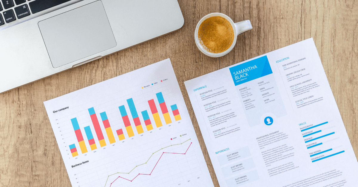 business reports with finance figures on top of desk next to laptop and coffee mug