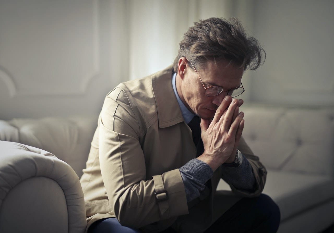 middle aged man with face in hands deep in thought